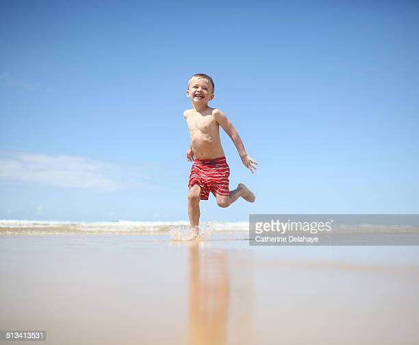 A 3 years boy running on the beach