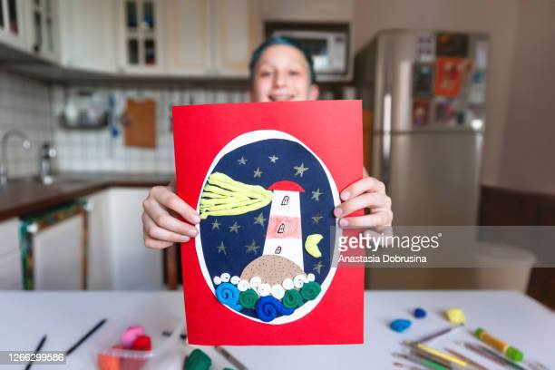 10 years boy showing his hand made card with lighthouse - 10 11 years stock pictures, royalty-free photos & images