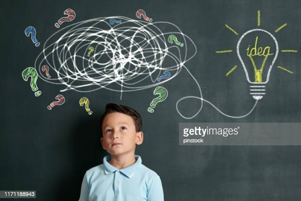 6-7 years child is finding solution on front of blackboard - 6 7 years stock pictures, royalty-free photos & images