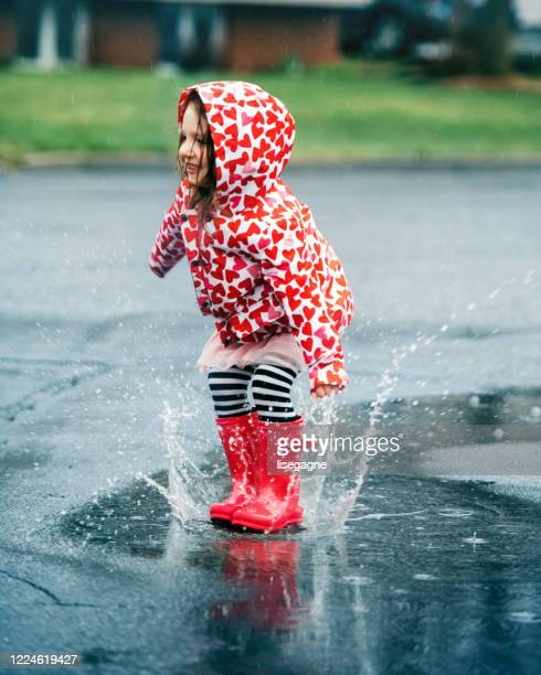 4 years little girl jumping in puddle - 4 5 years stock pictures, royalty-free photos & images