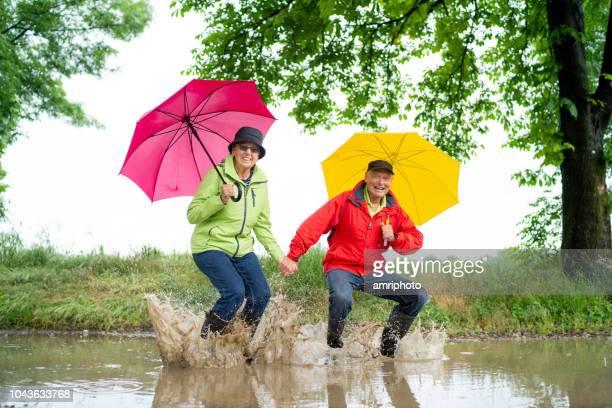 70 jaar oud regen actieve grappige gelukkig senioren paar springen in Plas