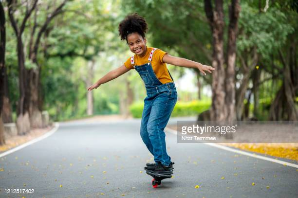 a 10 years old afro american girl skateboarding in the street at public park.  girl learning skateboard to play by self. - 10 11 years stock pictures, royalty-free photos & images