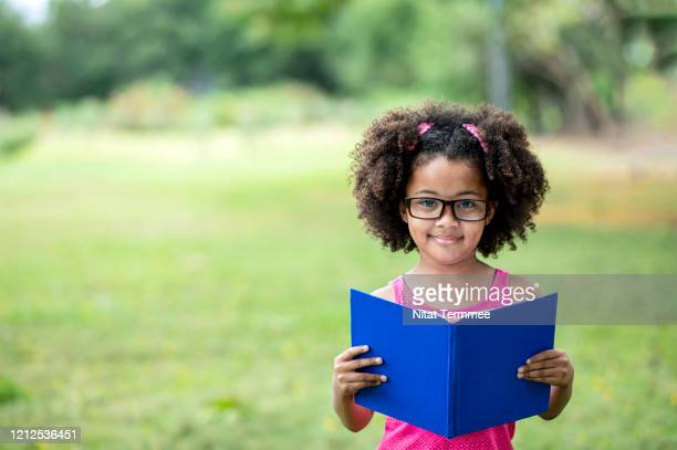 a 7 years old afro american little student girl reading book in the public park. education and learn in the park. - 6 7 years stock pictures, royalty-free photos & images