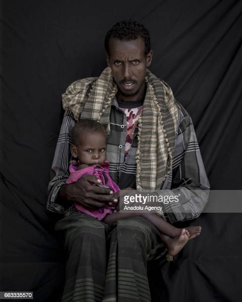 39 years old Aliyow Ibrahim Hassan fled from Owdiinle district 35 kilometers away from Bay due to drought holds his son Abdirashid Ali brahim who...