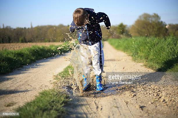 7 years old blond boy jumping in a mud puddle on a late afternoon of spring - 6 7 years stock pictures, royalty-free photos & images