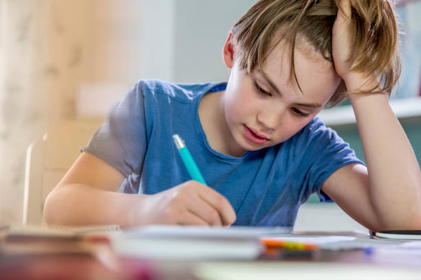 10 years old blonde school boy while doing his homework. - homework stock pictures, royalty-free photos & images