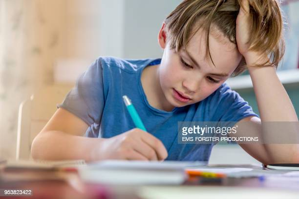 10 years old blonde school boy while doing his homework. - homeschool ストックフォトと画像