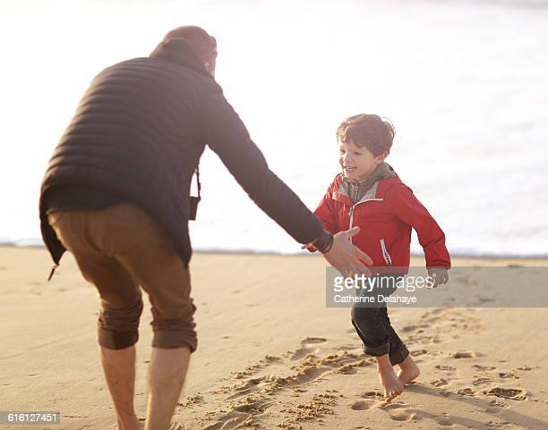 a 5 years old boy and his dad playing on the beach - delahaye stock photos and pictures