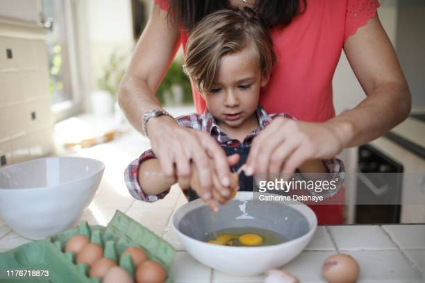 a 4 years old boy cooking at home with his mum - cuisine photos et images de collection