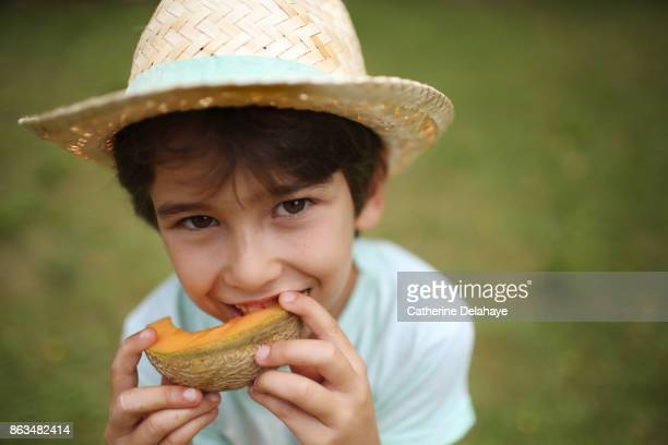 a 7 years old boy eating melon - 6 7 years stock pictures, royalty-free photos & images