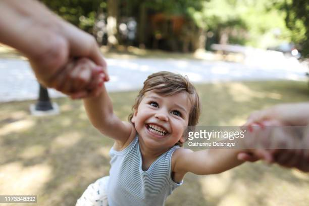 a 3 years old boy having fun in the arms of his mum - giochi per bambini foto e immagini stock