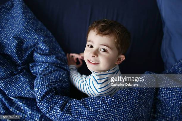 A 3 years old boy in his bed