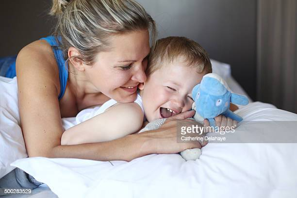 A 3 years old boy in his bed with his mom