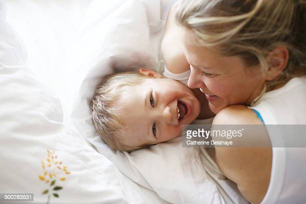 a 3 years old boy in his bed with his mom - delahaye stock photos and pictures