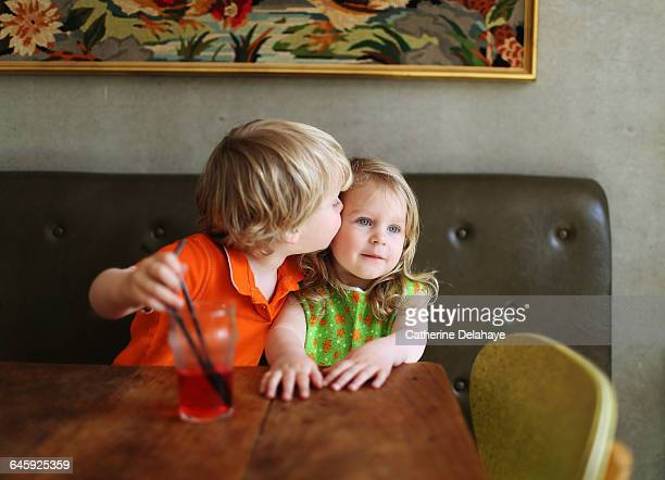 A 3 years old boy kissing a girl