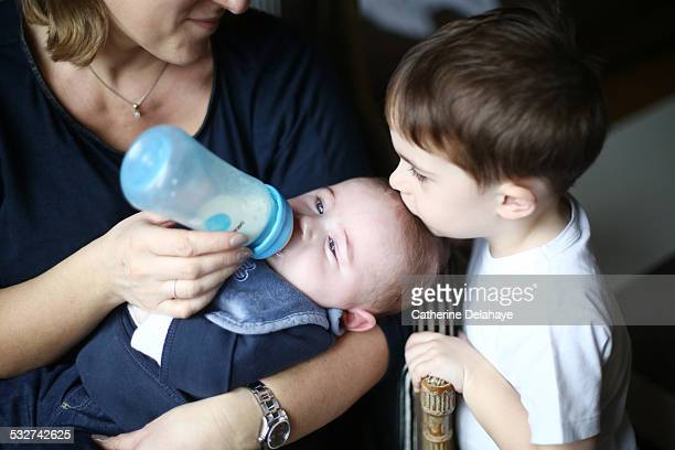 A 3 years old boy kissing his baby brother