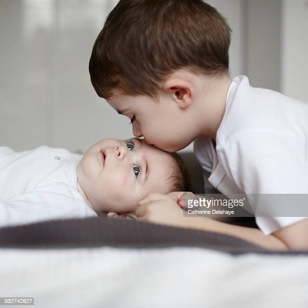 a 3 years old boy kissing his baby brother - 2 3 years stock pictures, royalty-free photos & images