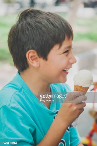 8 years old boy laughing and eating an ice cream - 8 9 years stock pictures, royalty-free photos & images