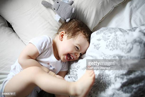 a 2 years old boy laughing in a bed - 2 3 years stock pictures, royalty-free photos & images