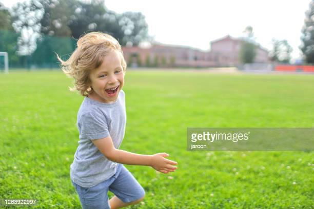4 years old boy on the grass - 4 5 years stock pictures, royalty-free photos & images