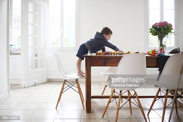 A 3 years old boy playing with cars on a table