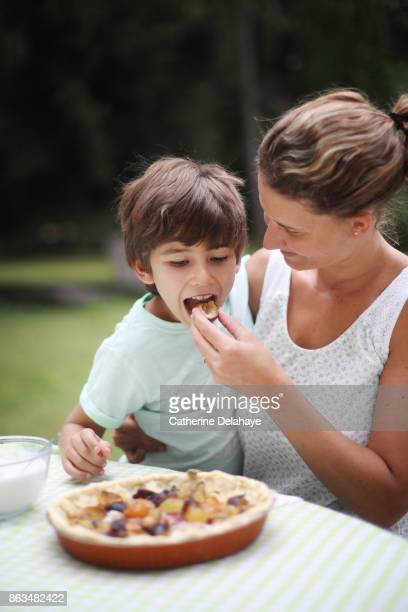 a 7 years old boy preparing a plum tart with his mum - 6 7 years stock pictures, royalty-free photos & images