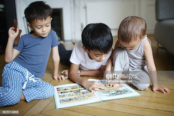 a 10 years old boy reading a book to his brothers - 10 11 years stock pictures, royalty-free photos & images
