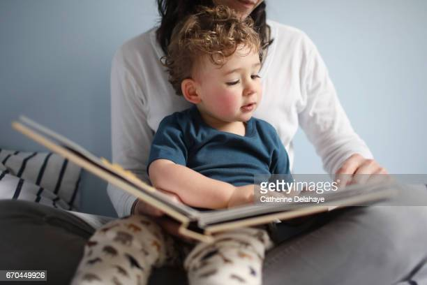A 2 years old boy reading a book with his mom