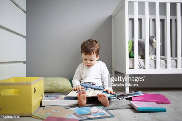 A 2 years old boy reading in his bedroom