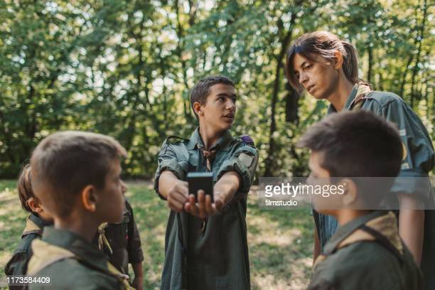 15 years old boy scout teaching boys and girls how to use compass - 14 15 years stock pictures, royalty-free photos & images