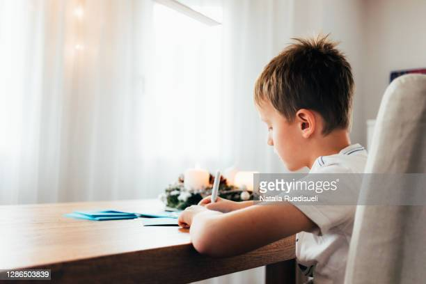a 9 years old boy sitting at the wooden table and writing christmas greeting cards. cozy ambience of a decorated house with advent wreath and window lights. - 8 9 years stock pictures, royalty-free photos & images