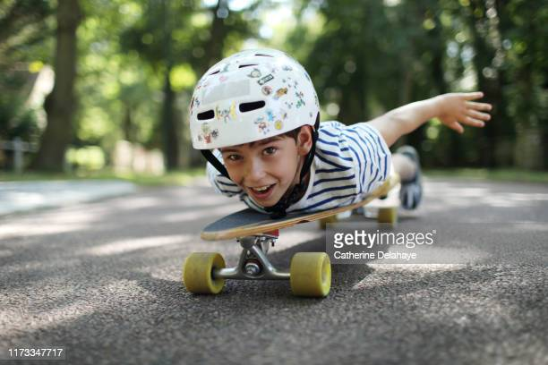 a 9 years old boy skateboarding in the street - 8 9 years stock pictures, royalty-free photos & images