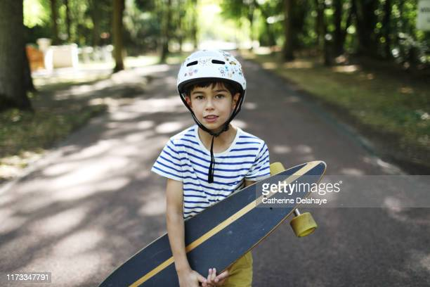 a 9 years old boy skateboarding in the street - 8 9 años fotografías e imágenes de stock