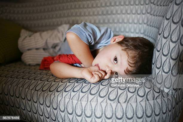 A 4 years old boy sucking his thumb on a sofa