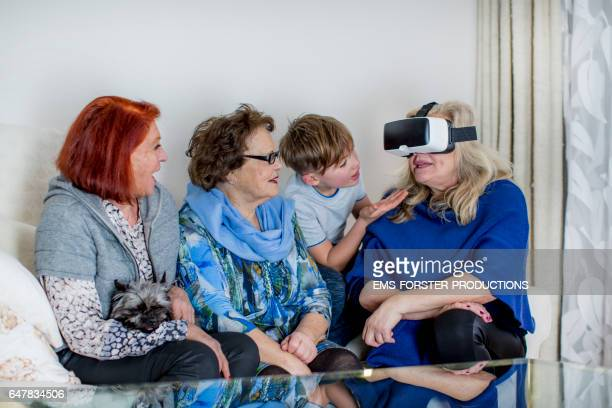 9 years old boy teaches grand mother and great grandmother and Bestager woman how to use VR glasses