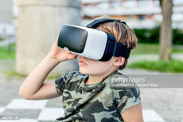 8 years old boy uses VR head set outside