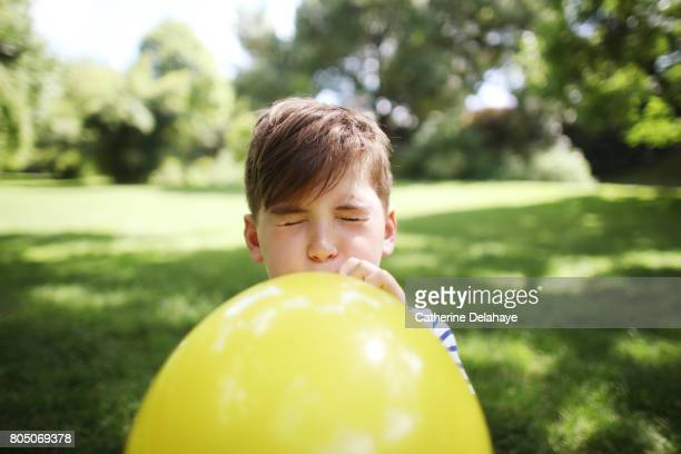 A 8 years old boy with a balloon in a park