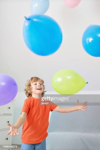 4 years old boy with colorful balloons indoors - 4 5 years stock pictures, royalty-free photos & images