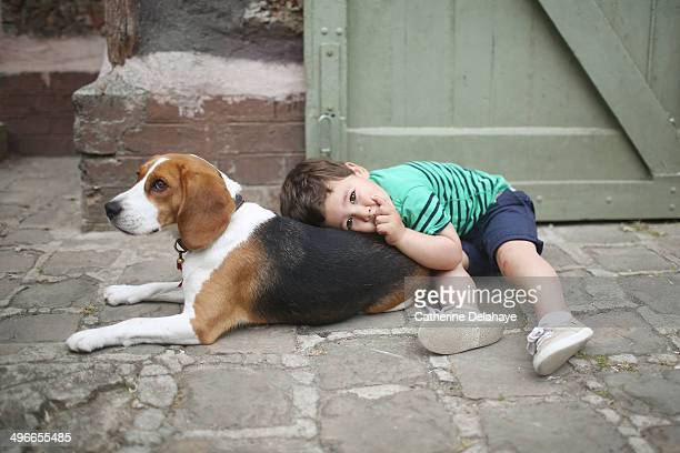 A 3 years old boy with his dog, a beagle