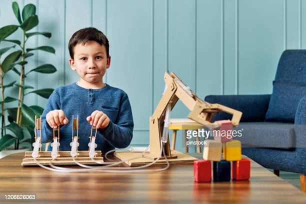6-7 years old child invented a robotic arm with cardboard and syringe. robotic is his homework. he is a successful student in elementary school. - inventor stock pictures, royalty-free photos & images