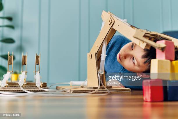 6-7 years old child invented a robotic arm with cardboard and syringe. robotic is his homework. he is a successful student in elementary school. - 6 7 years stock pictures, royalty-free photos & images