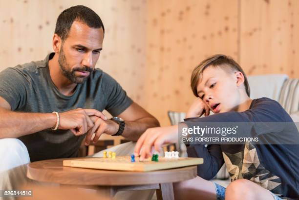 9 years old cute boy with blonde hair plays ludo parcheesi with his young father with dark hair and trimmed beard while digital detox in a living room with wooden walls, ludo board with tokens blurred in foreground.