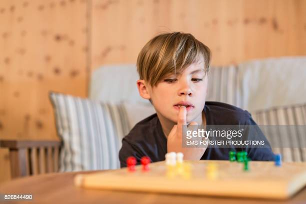 9 years old cute boy with blonde hair without brothers or sisters playing ludo parcheesi is very concentrated thinking about playing the game while digital detox in a living room with wooden walls, ludo board with tokens blurred in foreground.