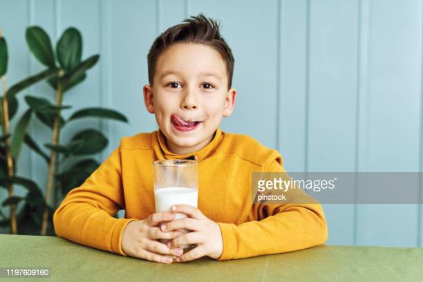6-7 years old cute child drinking milk on table. he knows that he needs to drink milk for healthy bones. he loves milk. - 6 7 years stock pictures, royalty-free photos & images