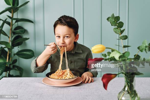 6-7 years old cute child eating spaghetti. he is happy. - 6 7 years stock pictures, royalty-free photos & images