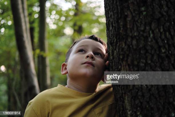 6-7 years old cute child listening tree and nature - 6 7 years stock pictures, royalty-free photos & images