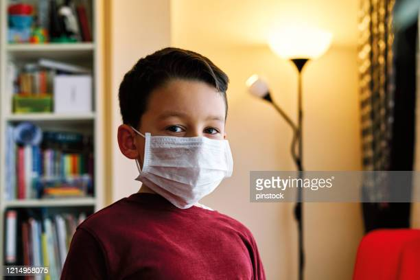 6-7 years old cute child staying at home for social distancing. he is boring but necessary for protection from coronavirus. - protective workwear stock pictures, royalty-free photos & images