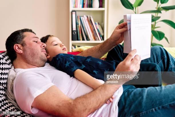 30-39 ans père lecture livre sur le canapé pour son enfant. - 30 39 years photos et images de collection