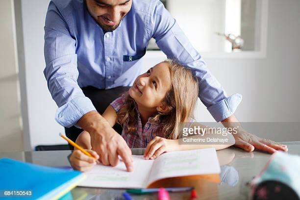 a 7 years old girl doing her homework with her dad - 8 9 years stock pictures, royalty-free photos & images