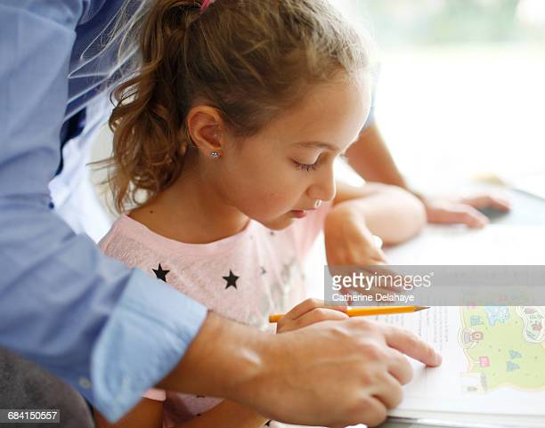 A 7 years old girl doing her homework with her dad
